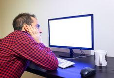 Den ängsliga mannen stirrar på kontorsdatoren på träsvart skrivbordmodell Den prack röda skjortan, LCD-skärmen, tangentbordet, mu royaltyfria foton