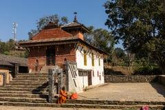 Den åldrades nepalien vallfärdar i orange ämbetsdräkt i templet av Bandipur i Nepal November 24 2016 Royaltyfri Foto