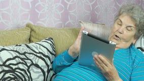 Den åldriga kvinnan rymmer en minnestavladator inomhus arkivfilmer