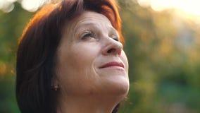 Den åldriga kvinnan ser till himlen stock video