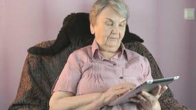 Den åldriga kvinnan sitter på en fåtölj bredvid en svart katt lager videofilmer