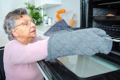Den åldriga kvinnan som kontrollerar mat lagade mat hon, den inre ugnen Fotografering för Bildbyråer