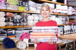 Den åldriga kvinnan som tycker om inhandlade hem- textiler i textil, shoppar arkivfoton