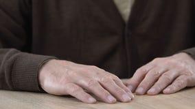 Den åldriga mannen suckar SAD, händer på tabellcloseupen, ensamhet i avgånghem arkivfilmer