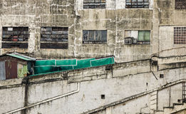Den åldriga tegelstenväggen med sprickor och hasar Royaltyfri Foto