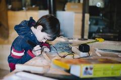 den 10-åriga pojken i ett seminarium för snickare` s lär hur man gör litet Fotografering för Bildbyråer