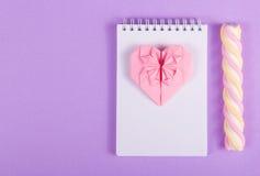 Den öppna anteckningsboken, hjärtaorigamin och marshmallowen klibbar på en purpurfärgad bakgrund Fotografering för Bildbyråer