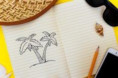 Den öppna anteckningsboken med en bild av en palmträd ligger på en uttrycksfull gul yttersida Arkivbilder