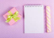 Den öppna anteckningsboken med en tom sida, valentinorigamin och marshmallowen klibbar på en bakgrund av prickar Royaltyfria Foton