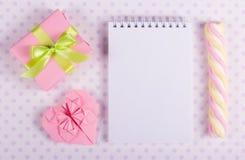 Den öppna anteckningsboken med en tom sida, valentinorigamin och marshmallowen klibbar på en bakgrund av prickar Arkivbild