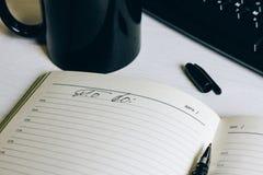 Den öppna anteckningsboken på tabellen bredvid tangentbordet royaltyfria bilder