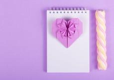 Den öppna anteckningsboken, valentinorigamin och marshmallowen klibbar på en purpurfärgad bakgrund Arkivfoton