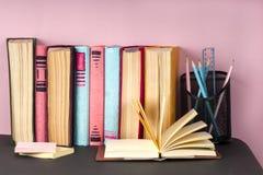 Den öppna boken, bunt av den färgrika inbundna boken bokar på den ljusa tabellen tillbaka skola till Kopiera utrymme för text Arkivfoto