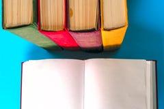 Den öppna boken, bunt av den färgrika inbundna boken bokar på den ljusa tabellen tillbaka skola till Kopiera utrymme för text Arkivbilder