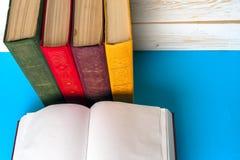 Den öppna boken, bunt av den färgrika inbundna boken bokar på den ljusa tabellen tillbaka skola till Kopiera utrymme för text Arkivbild