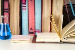 Den öppna boken, bunt av den färgrika inbundna boken bokar på den ljusa tabellen tillbaka skola till Kopiera utrymme för text Arkivfoton