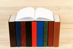 Den öppna boken, bunt av inbundna boken bokar på trätabellen Arkivbild