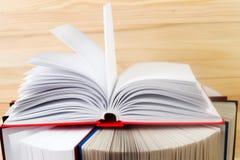 Den öppna boken, bunt av inbundna boken bokar på trätabellen Fotografering för Bildbyråer