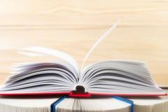 Den öppna boken, bunt av inbundna boken bokar på trätabellen Royaltyfria Foton