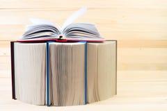 Den öppna boken, bunt av inbundna boken bokar på trätabellen Royaltyfria Bilder
