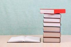 Den öppna boken, bunt av inbundna boken bokar på trätabellen Arkivbilder