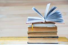 Den öppna boken, bunt av inbundna boken bokar på trätabellen Arkivfoton