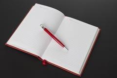 Den öppna boken och pennan Royaltyfri Foto