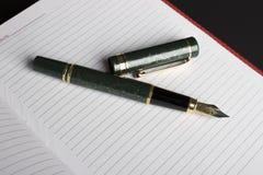 Den öppna boken och pennan Fotografering för Bildbyråer