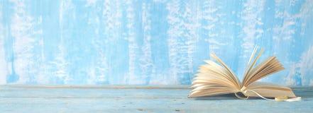Den öppna boken på blått målar bakgrund, panorama arkivbilder