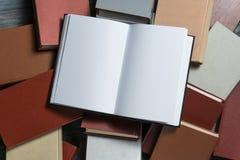 Den öppna bokinbundna boken på bunt bokar på träbakgrund Royaltyfria Foton