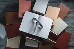 Den öppna bokinbundna boken på bunt bokar på träbakgrund royaltyfri bild