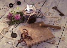 Den öppna dagboken med den gamla klockan, den svarta stearinljuset, vingpennan och medaljongen på planksBlackstearinljuset med da Royaltyfri Fotografi