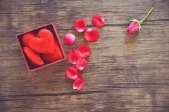 Den öppna gåvaasken med den röda närvarande asken för röd hjärta med full hjärta för gåvavalentindag och roskronblad blommar royaltyfri bild