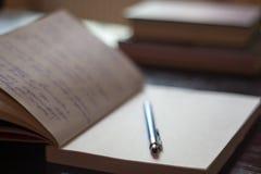 Den öppna notepaden med handskrivna anmärkningar med blåttpennan bokar i bet royaltyfri foto
