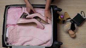 Den öppna påsen för kvinna` s på ett skrivbord med kläder och tillbehör, är hon packa och få klar att lämna, resa och lager videofilmer