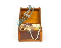 Den öppna skattbröstkorgen med armband, myntar, ringer och pryder med pärlor Arkivfoto