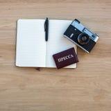 Den öppnade notepaden med pennan, filmkameran och ett rött certifikat med inskriften TRYCKER PÅ Fotografering för Bildbyråer