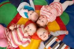 Den över huvudet sikten av behandla som ett barn att ligga på Mat At Playgroup arkivbilder