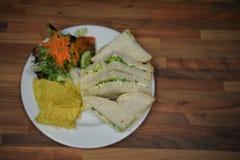 Den över huvudet sikten av matfotografi med en hemlagad lunch av ost- och löksmörgåsar och sidosallad tjänade som på en vit platt royaltyfri bild