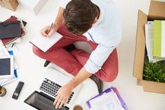 Den över huvudet sikten av startar upp affärsflyttning in i kontor Royaltyfri Foto