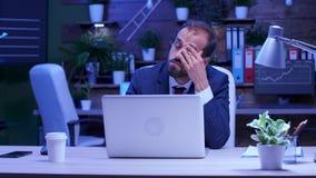 Den överansträngde affärsmannen sitter framme av datoren arkivfilmer