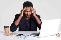 Den överansträngde stressiga mannen håller händer på huvudet, uppehällen stirrar ner, tröttas av konstant arbete på bärbar datord arkivbilder