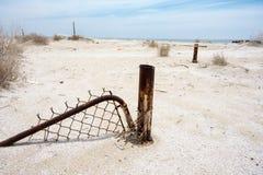 Den övergav staketporten sitter begravt i sanden i den Bombay stranden Kalifornien, en övergiven stad på det Salton havet royaltyfri foto