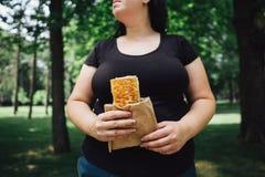 Den överviktiga kvinnan äter donerkebab som utomhus går Fotografering för Bildbyråer