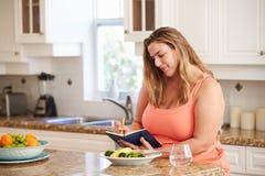 Den överviktiga kvinnan bantar på hålla mattidskriften Royaltyfri Foto