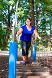 Den överviktiga kvinnan i klättring parkerar att göra sporten royaltyfria bilder