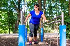 Den överviktiga kvinnan i klättring parkerar att göra sporten arkivbilder