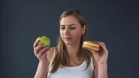 Den överviktiga kvinnan kan inte välja vad för att äta äpplet eller hamburgaren lager videofilmer