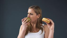 Den överviktiga kvinnan kan inte välja vad för att äta äpplet eller hamburgaren Hon väljer Apple äta för begrepp som är sunt stock video