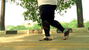Den överviktiga kvinnan lägger benen på ryggen spring på parkerar
